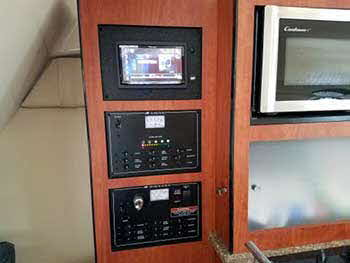 "Monterey Boat. Installed a Pioneer 7"" App Radio Receiver. Built a custom panel to house it seamlessly with the existing controls and appliances in the kitchen cabinet."