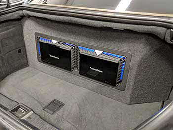 "2004 Mercedes Benz S55AMG - Installed Kenwood entertainment in the dash, Kenwood speakers in front & rear. Pulled the OEM sub out of the rear deck to allow the custom fabricated enclosure to vent through. Enclosure housed 2 pr Rockford 12"" subs and 2 Rockford amps. Trimmed with matching carpet/vinyl and blue accent lighting."