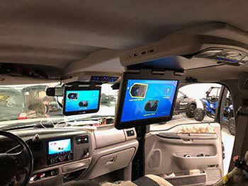 "We built custom overhead console to house 10"" & 13"" Audiovox overhead screens in this F250. Matched console to vehicles interior. Also installed Kenwood receiver and a back up camera."