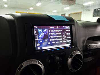 "Jeep Wrangler. Installed all Kenwood components: 6.8"" navigation entertainament system, amplifier, component & coax speakers, 12"" shallow sub in a vehicle specific enclosure and a back up camera."